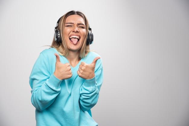 Ragazza bionda in felpa blu che indossa le cuffie, godersi la musica e divertirsi Foto Gratuite