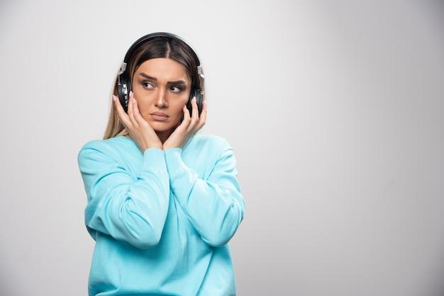 Ragazza bionda in felpa blu che indossa le cuffie e cerca di capire la musica Foto Gratuite