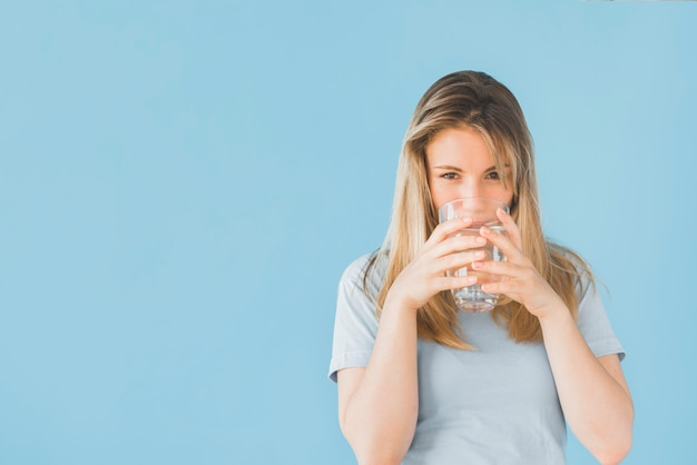 Blonde girl drinking glass of water Free Photo