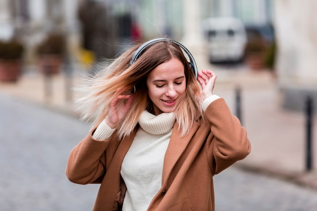 Blonde girl enjoying music on headphones Free Photo