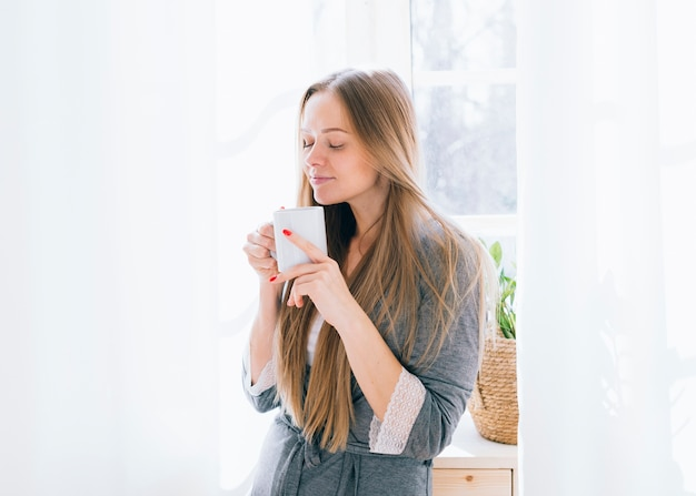 Blonde girl having coffee in the morning Free Photo