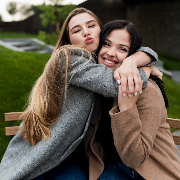 Blonde girl hugging her friend Free Photo