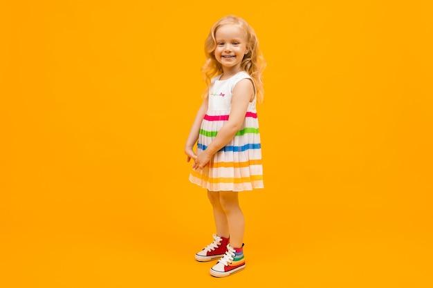Блондинка в ярком полосатом летнем платье Premium Фотографии