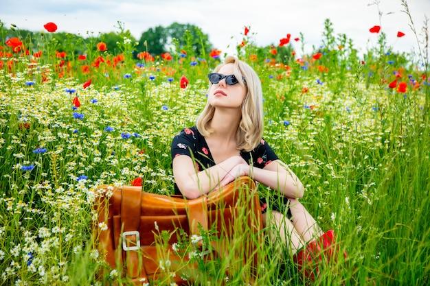 夏にはポピーフィールドでスーツケースを美しいドレスでブロンドの女の子 Premium写真