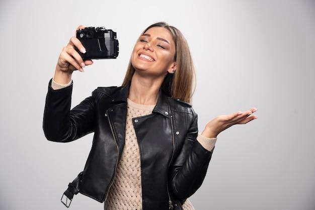 카메라와 함께 그녀의 Selfies를 복용 검은 가죽 재킷에 금발 소녀. 무료 사진