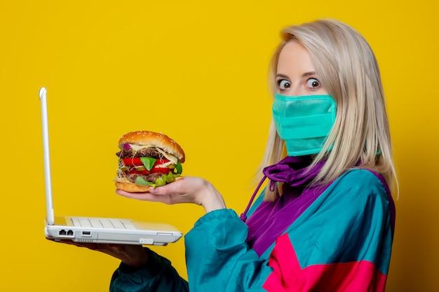 Блондинка в маске с гамбургером и ноутбуком Premium Фотографии