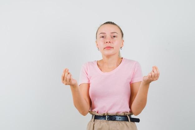 Tシャツ、お金のジェスチャーをしているズボン、正面図のブロンドの女の子。 無料写真