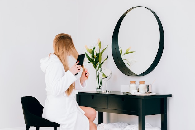 Blonde girl looking at her reflection Free Photo