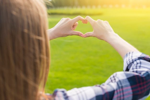 Blonde girl making a heart with her hands Free Photo
