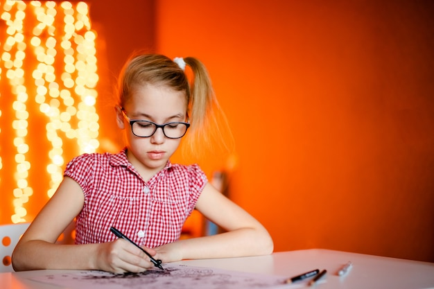 Blonde girl in the pink dress and big black glasses drawing santa claus. new year theme Premium Photo