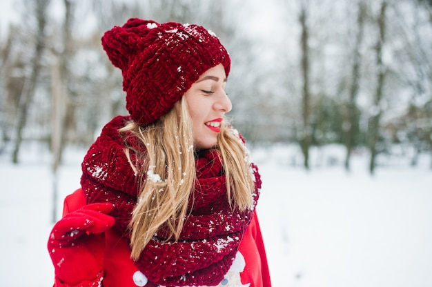 Blonde girl in red scarf, hat and santas sweater posing at park on winter day. Premium Photo