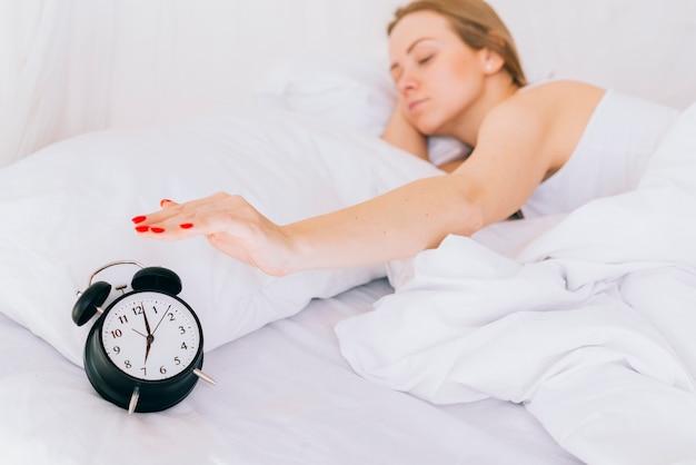 Blonde girl setting off the clock alarm Free Photo