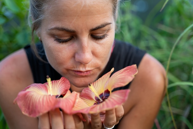 Blonde girl smelling some exotic flowers in her hands Premium Photo
