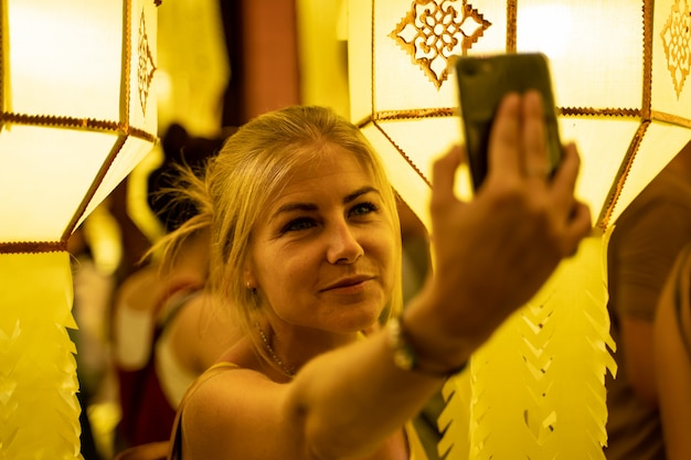 Blonde girl in a strapless dress surrounded by chinese lanterns at night making a selfie Free Photo
