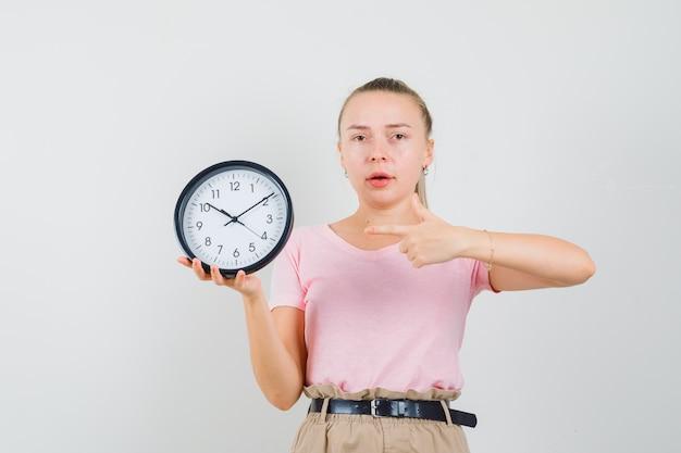 Ragazza bionda in t-shirt, pantaloni che punta all'orologio da parete e sembra ragionevole, vista frontale. Foto Gratuite
