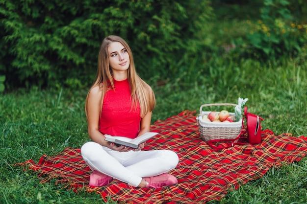 Блондинка думает о жизни в парке со своей любимой книгой. Premium Фотографии