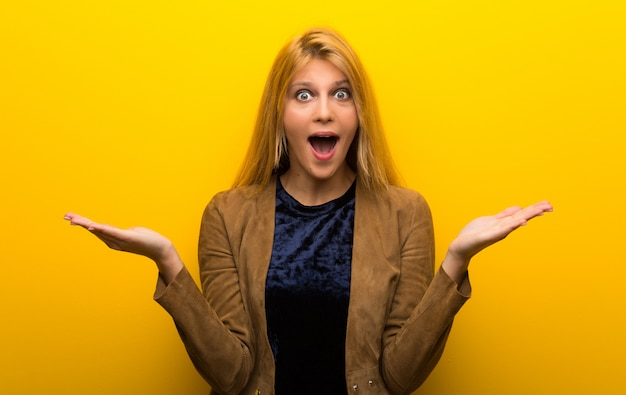 Blonde girl on vibrant yellow background with surprise and shocked facial expression Premium Photo
