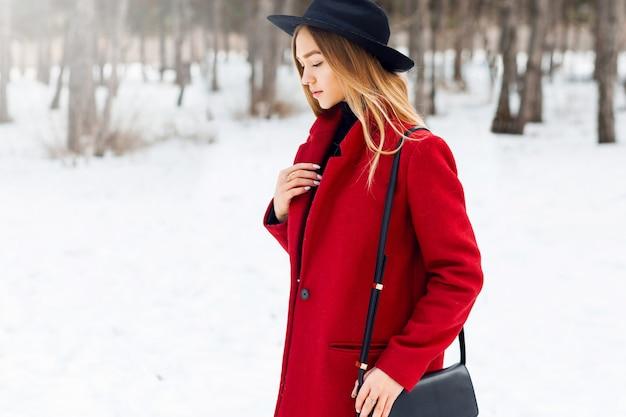 雪原に赤いコートを着ているブロンドの女の子 無料写真