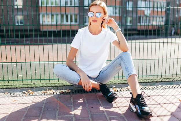 Blonde girl wearing t-shirt and glasses posing against street Premium Photo