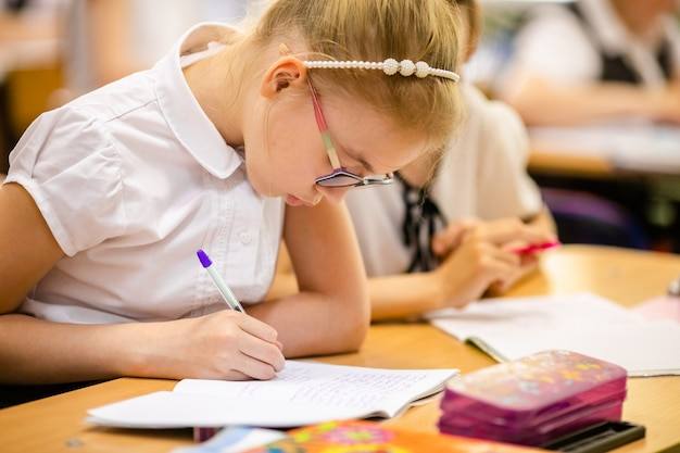 Blonde girl with big glasses sitting in classroom, studing, smiling. education on elementary school, first day at school Premium Photo