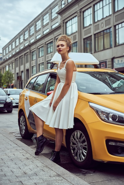 Blonde girl with flyaway hair in the background of new york city street with taxi cabs. Premium Photo