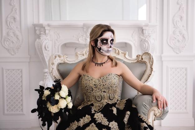 砂糖の頭蓋骨とブロンドの女の子を作る。死者の日またはハロウィーン Premium写真