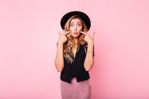 Ragazza bionda con il viso a sorpresa in piedi sul muro rosa. indossa un abito elegante con paillettes. emozioni stupite. Foto Gratuite