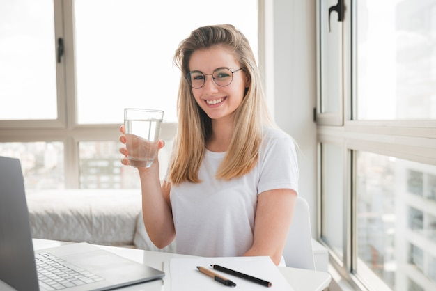 Blonde girl at work drinking water Free Photo