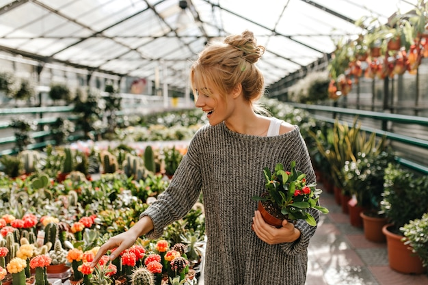 笑顔のブロンドの髪の女性は、美しい植物を手に持ってサボテンを選びます。 無料写真