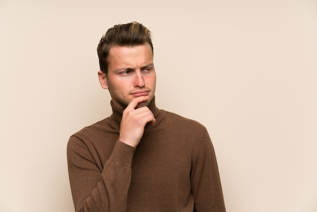 Blonde handsome man over isolated wall thinking an idea Premium Photo