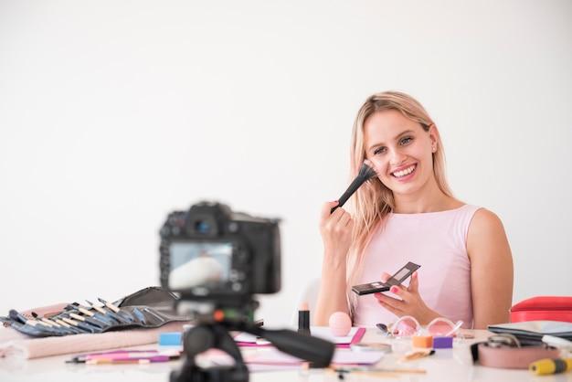 Blonde influencer recording make up video Free Photo