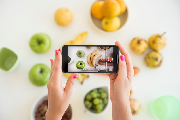 Blonde influencer taking picture of fruit Free Photo