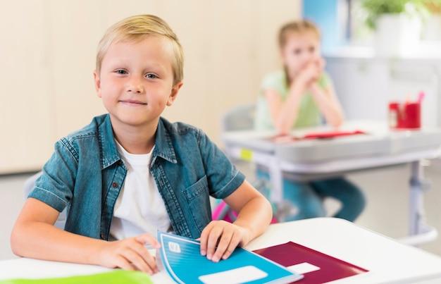 Блондинка ребенок сидит за своим столом Бесплатные Фотографии