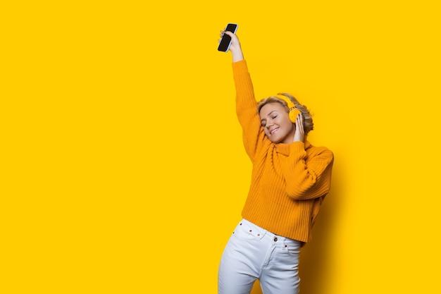 ヘッドフォンを使用して音楽を聴きながら、空きスペースのある黄色の壁で踊る金髪の女性 Premium写真