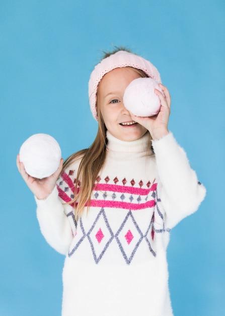 Белокурая маленькая девочка закрыла лицо снежком Бесплатные Фотографии