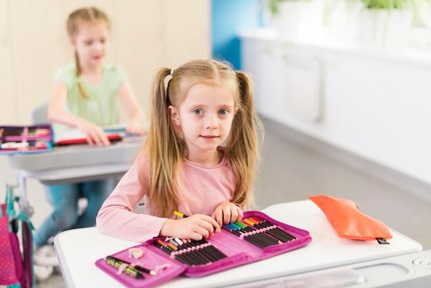Блондинка маленькая девочка с пеналом на столе Бесплатные Фотографии
