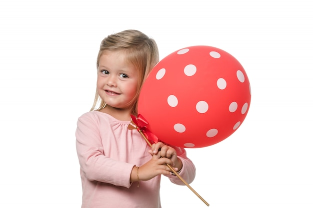 Blonde little girl smiling to camera with a balloon Premium Photo