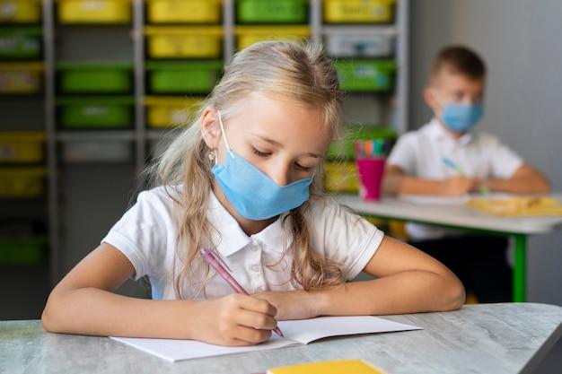 Bambina bionda che scrive mentre indossa una mascherina medica Foto Gratuite