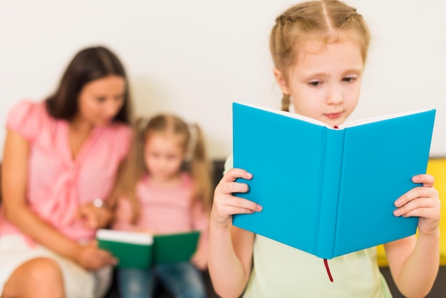 Блондинка маленький ребенок читает синюю книгу Premium Фотографии