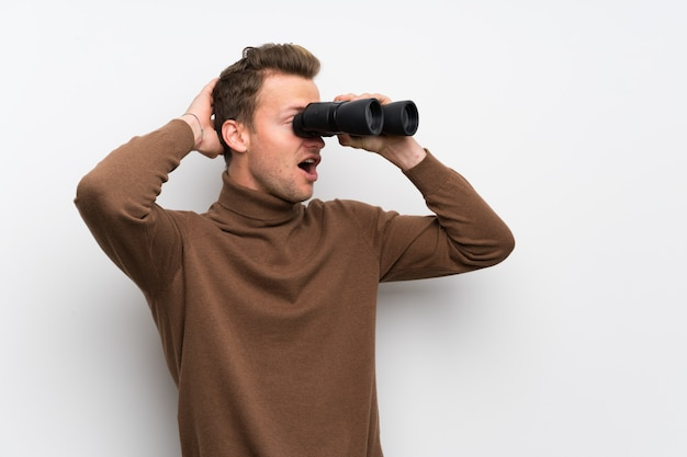 Blonde man over isolated white wall and looking in the distance with binoculars Premium Photo