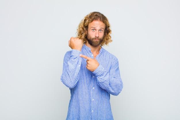 Светловолосый мужчина выглядит нетерпеливым и злым, указывая на часы, прося пунктуальности, хочет быть вовремя Premium Фотографии