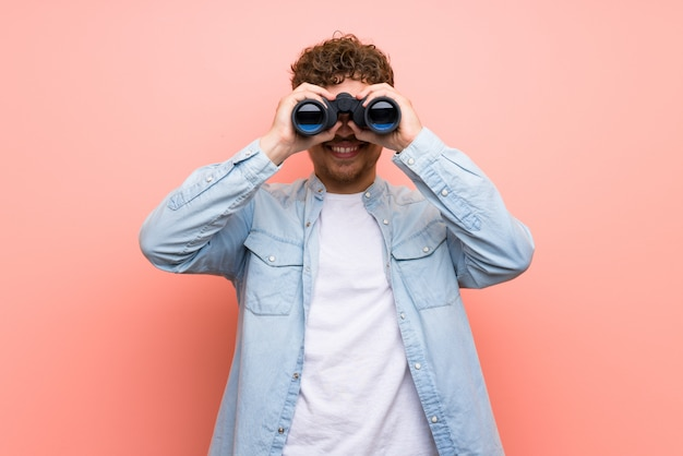 Blonde man over pink wall and looking in the distance with binoculars Premium Photo