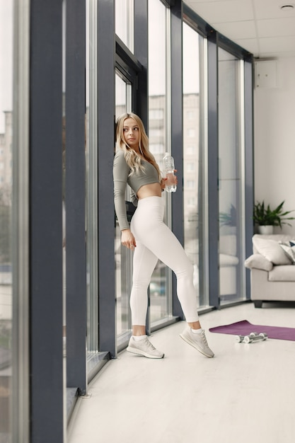 Posa bionda. signora in una tuta sportiva. donna a casa vicino alla finestra. Foto Gratuite