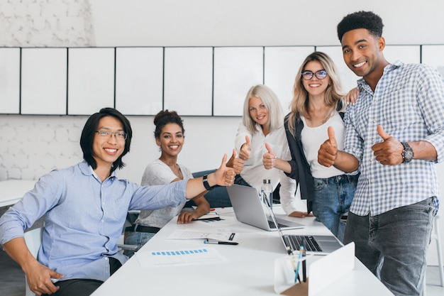 Blonde secretary sitting on table while office workers posing with thumbs up. indoor portrait of happy asian manager in trendy shirt smiling in conference hall with foreign partners. Free Photo