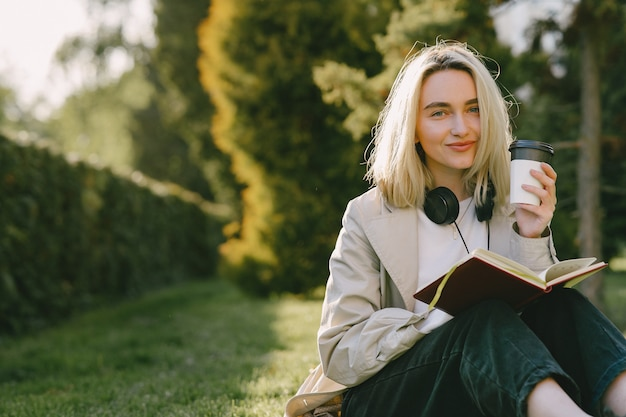 Блондинка сидит на траве с наушниками Бесплатные Фотографии