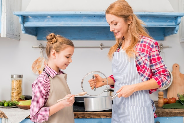Blonde smiling female showing cooking pot to her daughter in the kitchen Free Photo