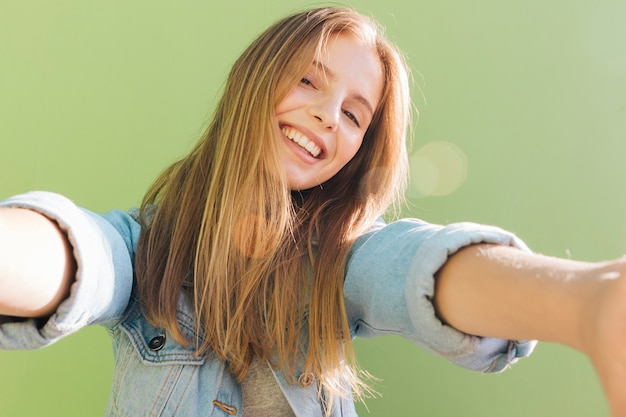 Blonde smiling young woman in sunlight taking selfie against green background Free Photo
