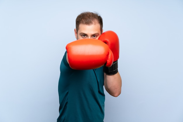 Blonde sport man over blue wall with boxing gloves Premium Photo