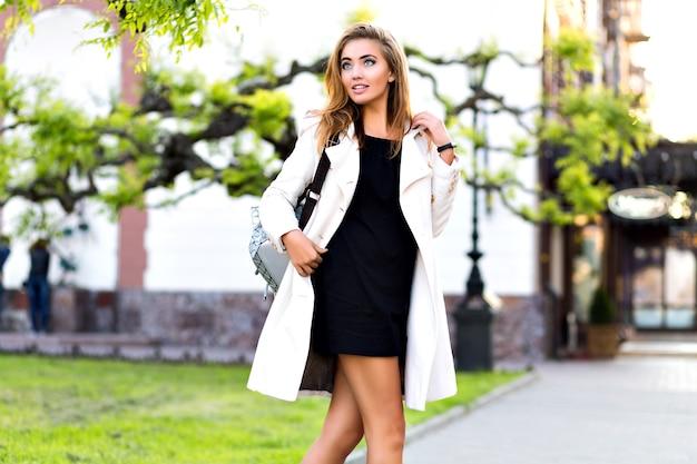 市内中心部で一人歩き、カジュアルなエレガントなコートとドレスを着て、一人で買い物をするストリートスタイルのファッションを作る金髪の見事な女性。 無料写真