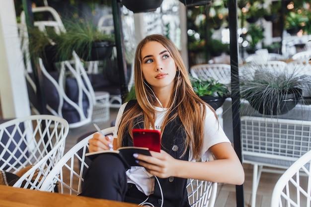 カフェで音楽を聴いている金髪の成功した女の子 Premium写真